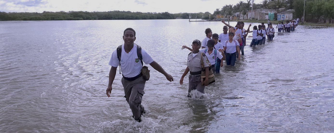 An image showing several youth in uniform in a single file line walking in ankle-deep water in what appears to be a lake or inlet.